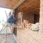 A Rwandan mason lays a column of bricks around a future window.